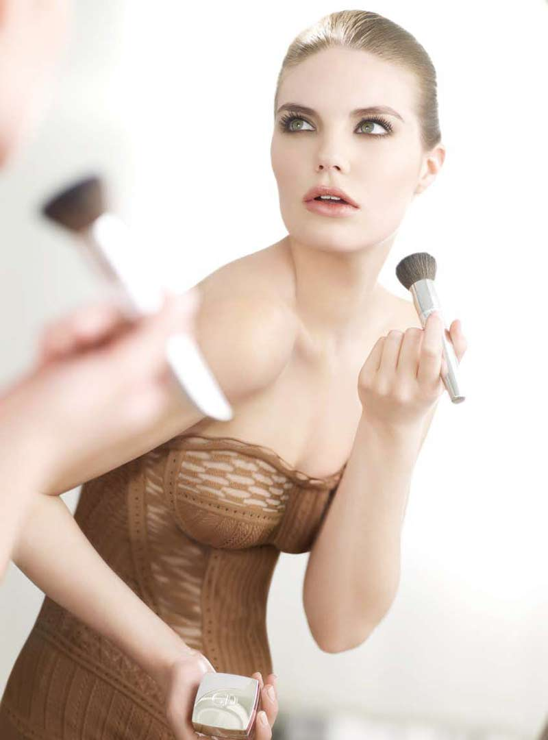 Model putting make-up on while looking in the mirror